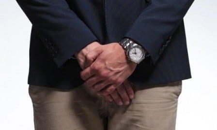 мужчина держит руки в паху
