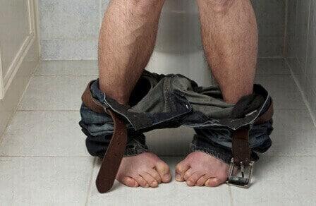 мужчина сидит в туалете