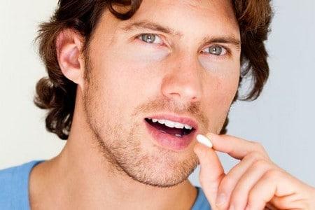 Мужчина кладет таблетку в рот