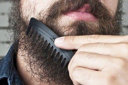 Мужчина расчесывает бороду