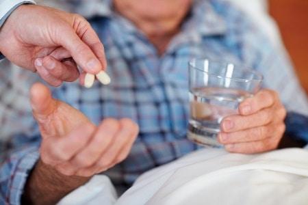 таблетки и стакан с водой в руке