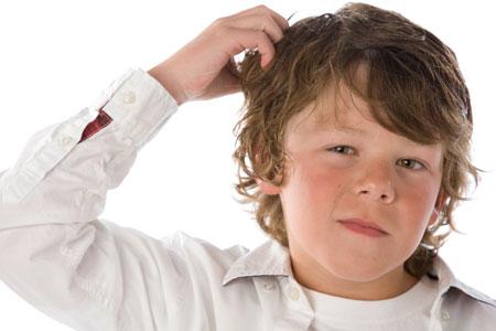 мальчик чешет голову