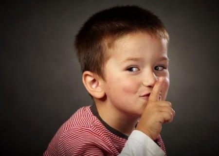 мальчик держит указательный палец у рта