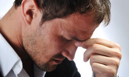 мужчина держит пальцы на переносице