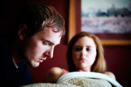 мужчина сидит возле лежащей жены