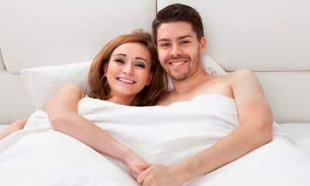 парень и девушка улыбаются в постели