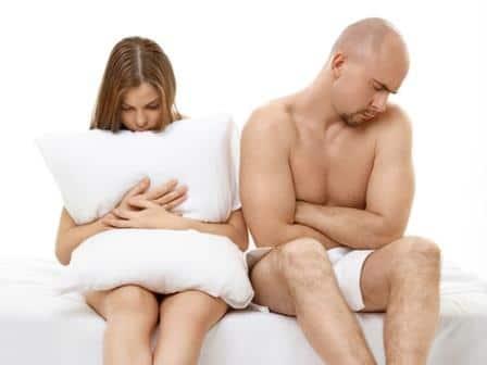 женщина держит подушку и сидит рядом с мужчиной