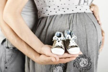 беременная держит детские пинетки