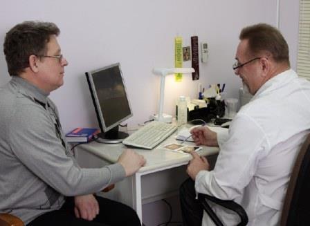 врач показывает мужчине на бумажку
