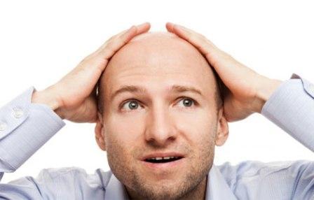 лысый мужчина держит руки на голове