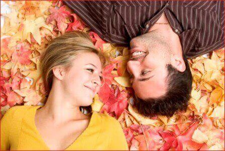 мужчина и женщина ледат на осенних листьях