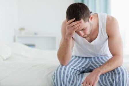 мужчина сидит на краю кровати и держится за голову