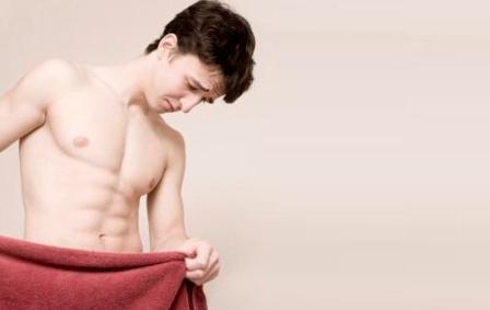парень прикрылся полотенцем и смотрит вниз