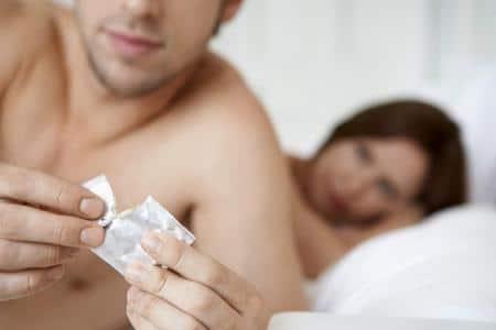 мужчина разрывает упаковку презерватива