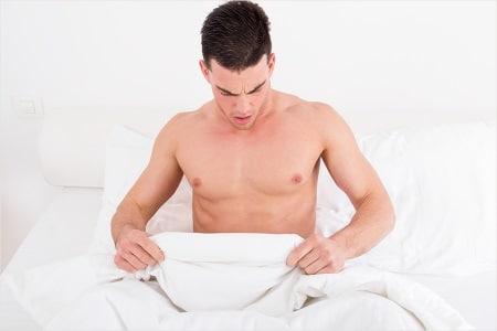 мужчина смотрит под одеяло