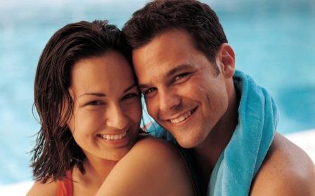 девушка и парень улыбаются и смотрят в камеру