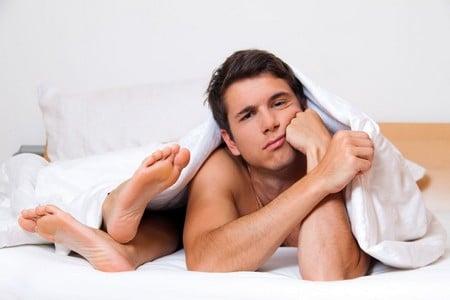 Грустный мужчина лежит в кровати