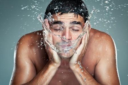 Мужчина моет лицо