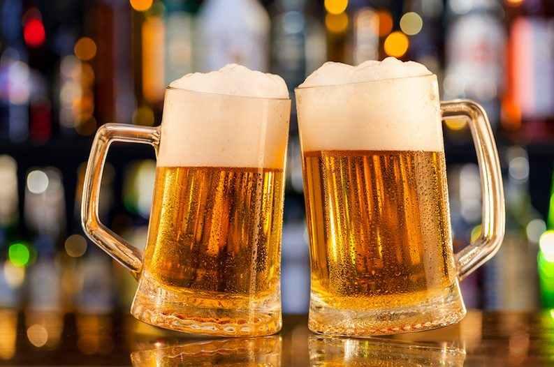 две большие кружки пива на барной стойке
