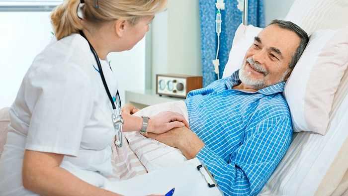 Мужчина лежит на кровати в палате и беседует с доктором