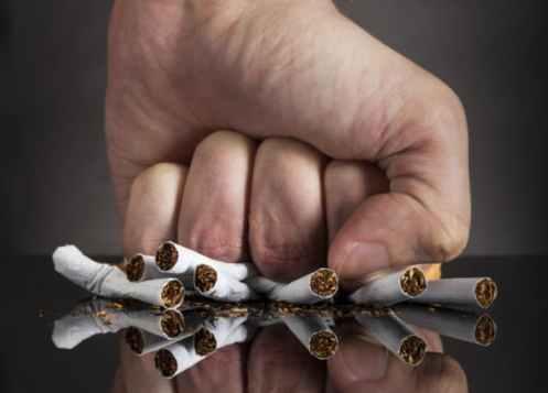 кулак мужчины сдавливает горку сигарет