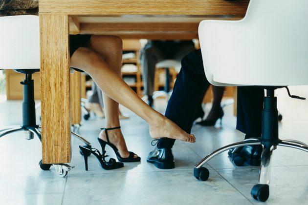 женщина флиртует с мужчиной ногой под столом
