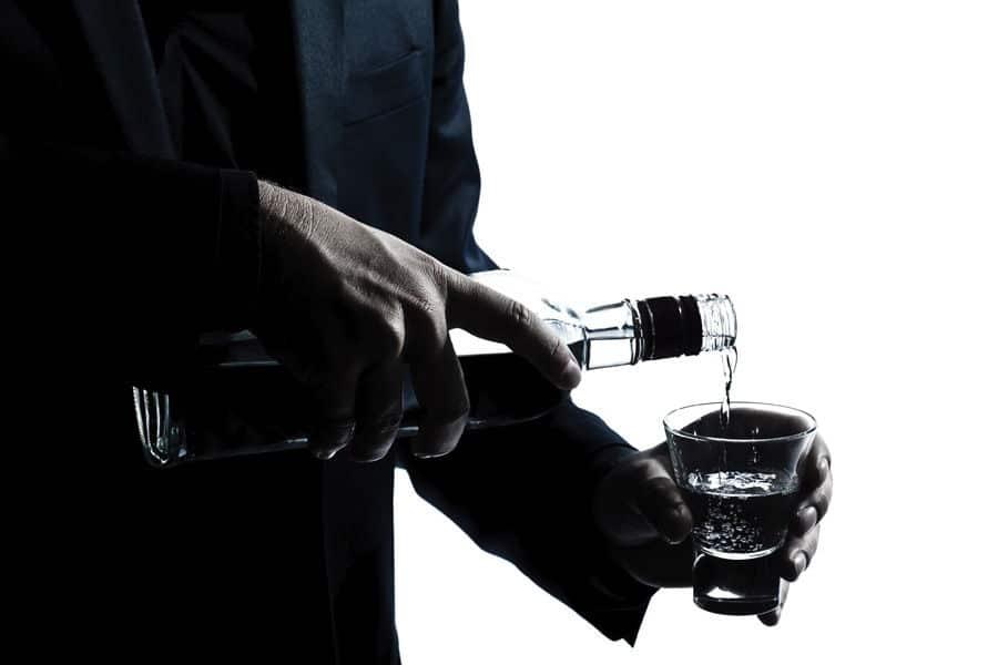 мужчина наливает алкоголь в чарку