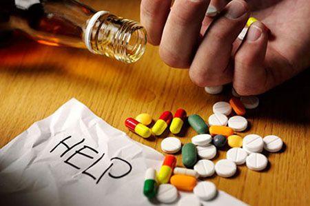 ладонь  мужчины, рассыпанные медикаменты и опрокинутая бутылка