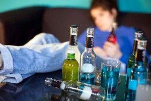 бутылки со спиртным и пьяная девушка на заднем фоне