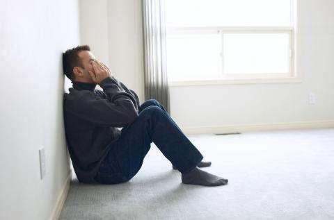 парень сидит на полу в пустой комнате