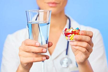 врач протягивает стакан с водой и таблетки